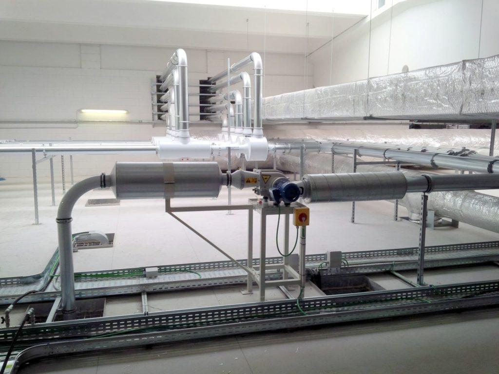 Sistema di taglio rifili in locale tecnico a soppalco del reparto produzione con camera bianca.